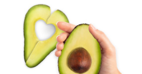 Hand holding sliced Avocado with Pit & another slice with heart cut-out