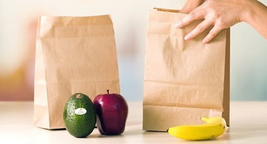Placing an unripe Avocado in a paper bag