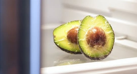Avocado halves wrapped in saran wrap inside a refrigerator