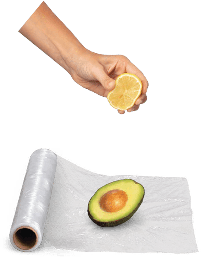 Lemon being squeezed on half of an Avocado